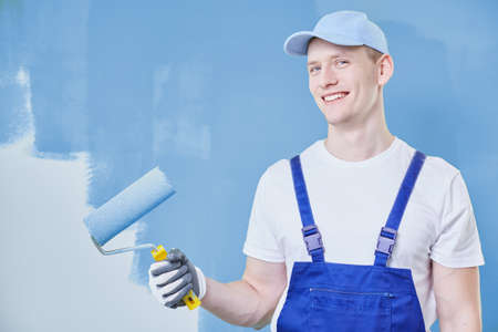 Schilder met een rol in zijn hand die zich tegen amost geschilderde blauwe muur bevindt Stockfoto