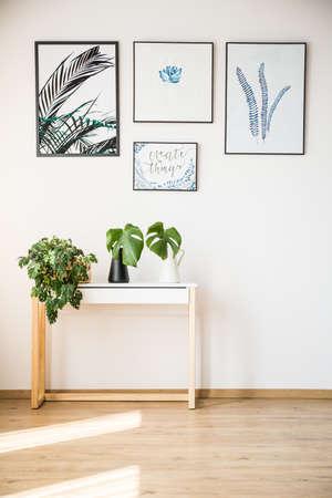 植物の壁のポスターの下の小さなテーブルの上に立って