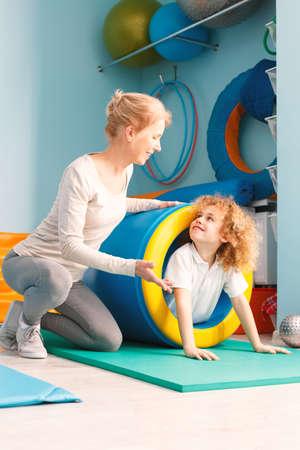 Glimlachende jongen die sensorisch integratiemateriaal en zijn therapeut gebruiken die hem helpen