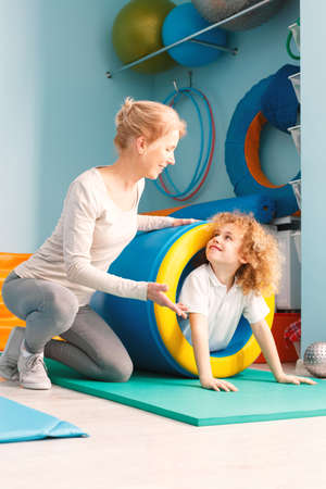 Smiling boy using sensory integration equipment and his therapist helping him Stock Photo