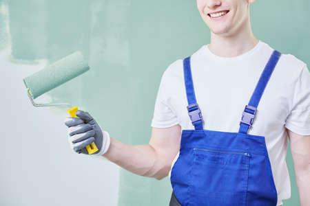 Professionele jonge schilder die een rol houdt en een muur schildert Stockfoto - 81948159