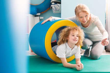 小さな男の子に新しい運動を説明するプロのセラピスト
