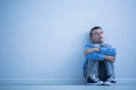 Eenzame autistische kind zittend op een vloer in een kamer Stockfoto