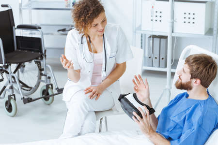 Young bearded man with VR goggles talking to smiling female doctor
