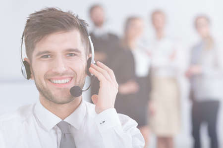 customer service representative: Smiling handsome man wearing headset and his colleagues standing behind him Stock Photo
