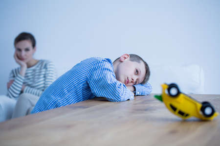 落ち込んでいる少年と木製のテーブル付きの部屋で母親の悲しい