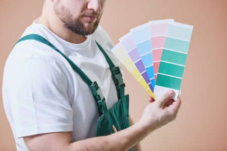 Young house painter against brown wall with color palettes in his hand