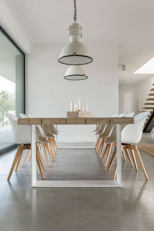 Minimalistic dining zone in open space of big modern house