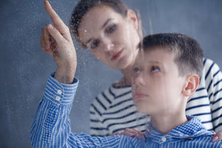 Sad boy looking through the window on a rainy day and his mom standing behind him Stock Photo - 81928630