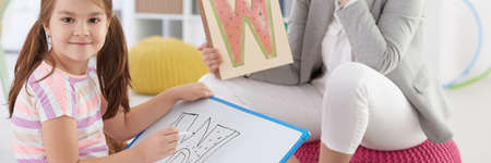Girl learning letters with school counsellor on additional classes Stock Photo