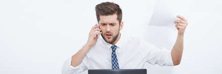 pedant: Businessman at work using laptop and making a phone call Stock Photo