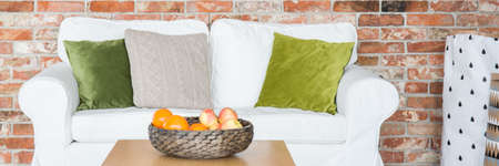 White sofa with green pillows in lounge with red brick wall