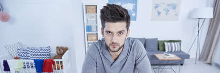 overtired: Single man in living room overworked by home duties Stock Photo