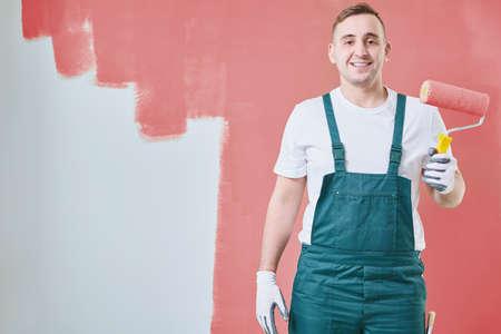 Glimlachende jonge huis schilder met een rol in zijn hand