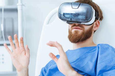 Young male bearded patient in futuristic modern VR goggles in hospital