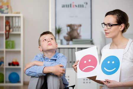 Droevige autistische jongen en zijn psycholoog tijdens een vergadering Stockfoto