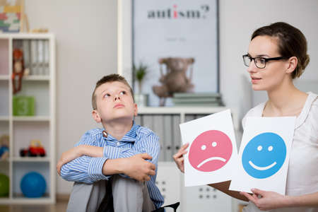 Sad autistic boy and his psychologist during a meeting Stock Photo - 81928734