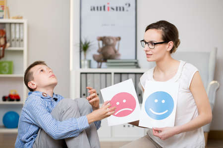 Professional psychologist working with autistic boy in her office Stock Photo