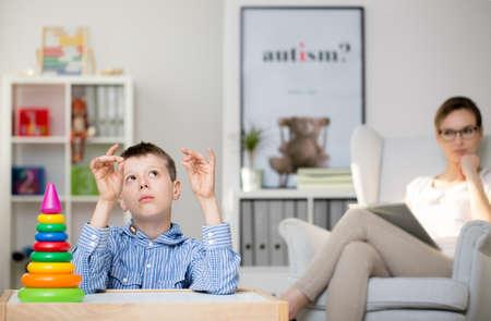 Professionele psycholoog die een autistische jongen in haar kantoor observeert Stockfoto