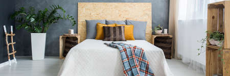 Grey wall and wooden decoration in cozy bedroom Stock Photo