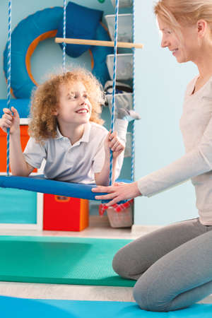 Little boy using therapy swing and smiling to his therapist Stock Photo