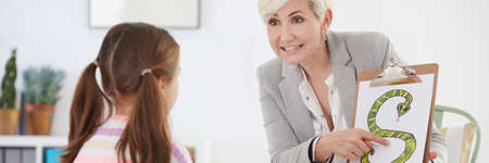 Female child therapist having educational classes of articulation with little girl