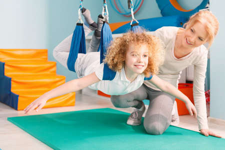 remedial: Boy and his therapist exercising during sensory integration therapy