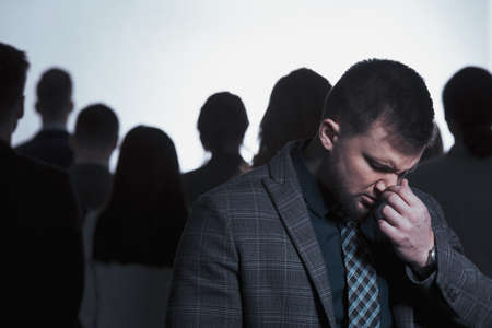 Man in despair and anonymous crowd of people Stock Photo