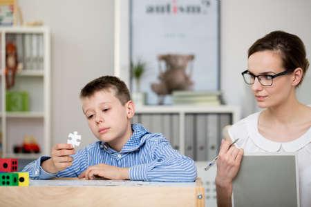 彼女の事務所で自閉症の少年についてメモを取る若い心理学者