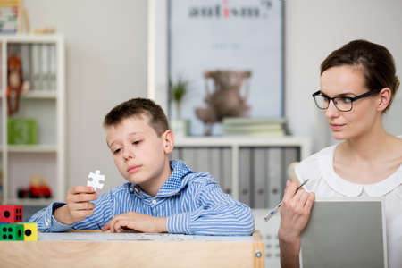 Young psychologist taking notes about an autistic boy in her office