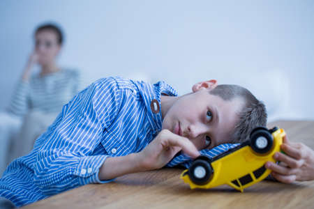 Sad autistic boy playing with toy car on wooden table