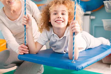 Happy little boy laying on therapy swing Banco de Imagens - 81928773