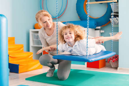 Woman helping a smiling boy to exercise on a therapy swing 스톡 콘텐츠