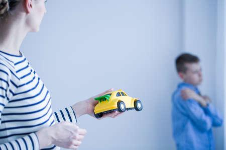 Mama geeft speelgoedauto aan haar verdrietige zoon in een kamer