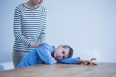 Sad autistic boy lying on a table and his mother standing next to him Stock Photo