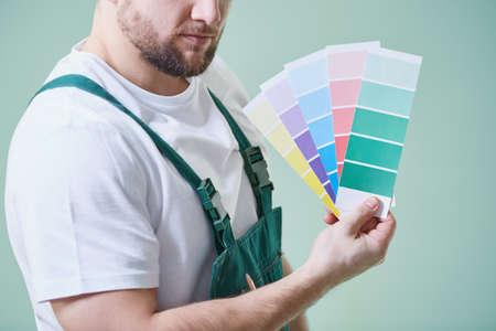 Jonge man draagt overalls en houdt kleurstalen