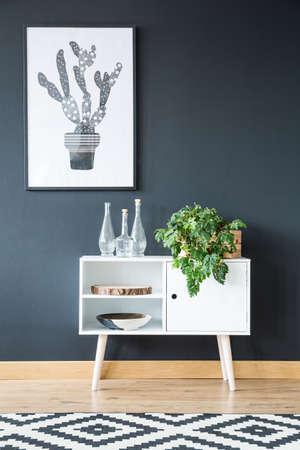 黒の壁に立っている植物で白い食器棚