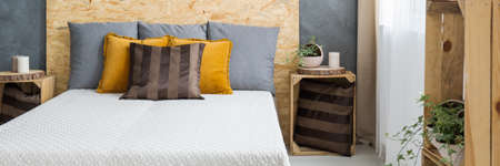 Comfortable bed with pillows and wooden osb headboard Stock Photo