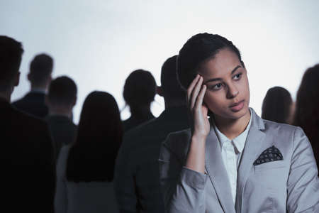 Tired businesswoman having headache, standing in anonymous crowd