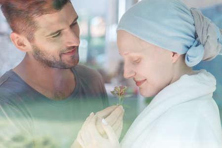 Giovane donna ammalata che odora un fiore fresco dal suo marito Archivio Fotografico - 82086479