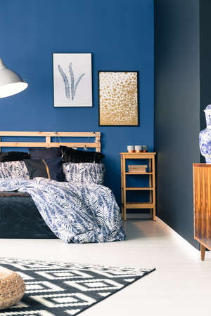 bedhead: Black and blue bedroom with wooden furniture