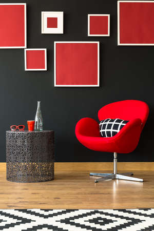 Black and red furniture and wall full of frames
