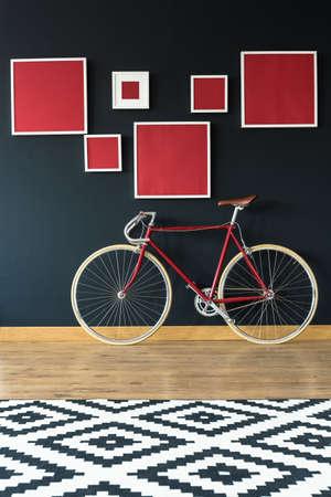 Bicicleta roja con estilo en apartamento con pared negra Foto de archivo - 82086476