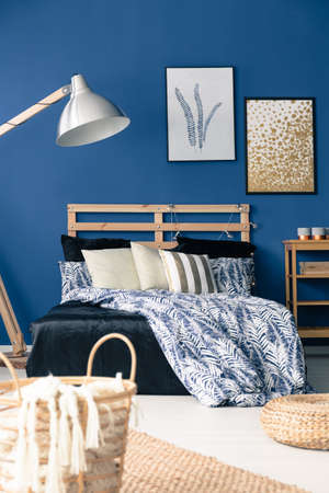 Dark blue bedroom with natural wooden furniture