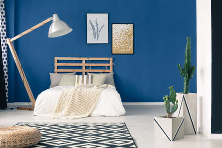 bedhead: Stylish gold and white bedclothes in blue bedroom