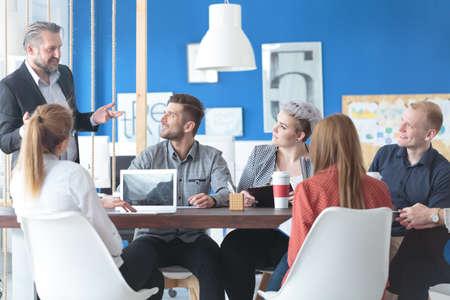 Team van jonge medewerkers luistert graag naar hun toespraak Stockfoto