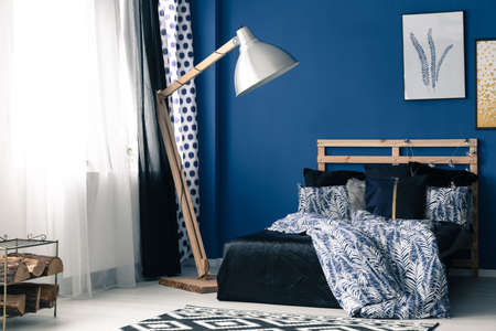 bedhead: Simple blue bedroom with modern wooden furniture Stock Photo