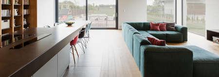 Ruime woonkamer verbonden met houten vloer verbonden met eetzaal en keuken. Op de achtergrond grote ramen met uitzicht naar buiten Stockfoto