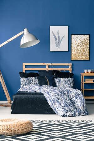 Bed met houten hoofdeinde op blauwe muur