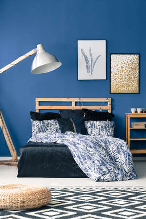 bedhead: Bed with wooden bedhead on blue wall